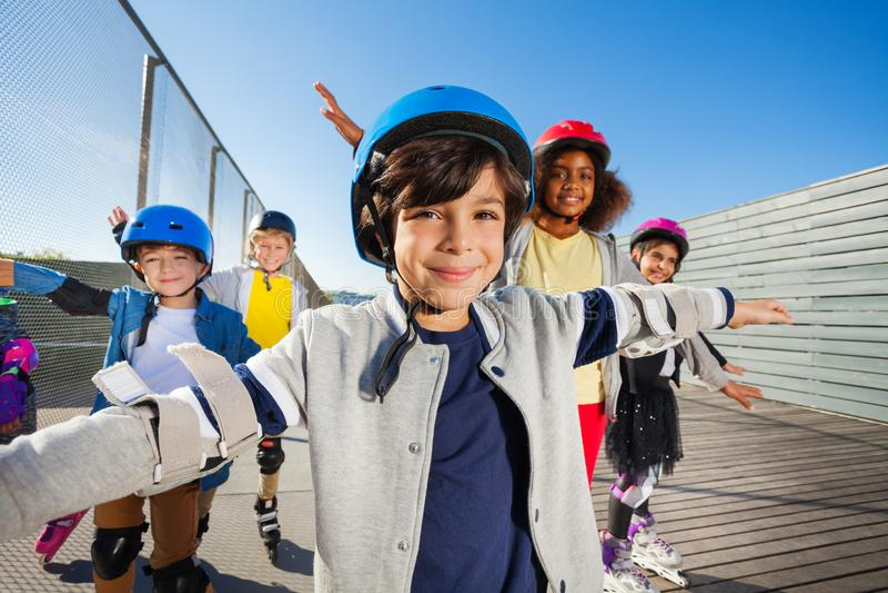rollerblading与户外朋友的青春期前的男孩 免版税库存照片