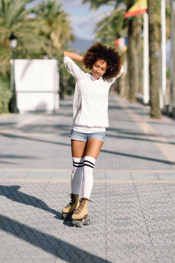 rollerblading在海滩散步wi的溜冰鞋的黑人妇女 库存照片