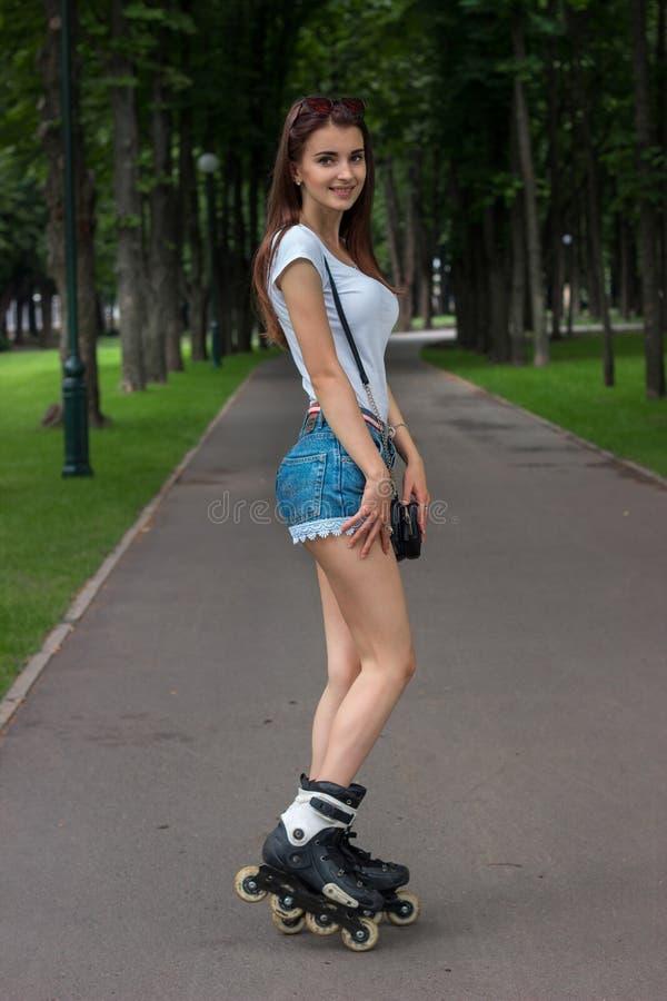 rollerblading牛仔布的短裤的美丽的微笑的女孩 免版税库存图片