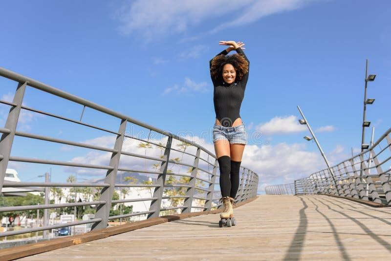 蓬松卷发乘坐户外在都市桥梁的溜冰鞋的发型妇女 免版税库存照片