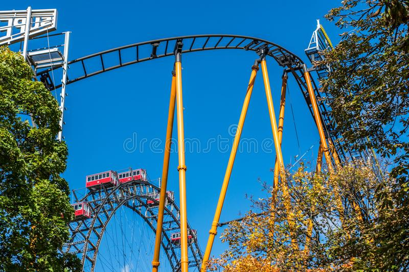 A rollercoaster and the world famous Weiner Riesenrad giant Ferris wheel of Prater Park in Vienna. Prater Park is home to royalty free stock photos