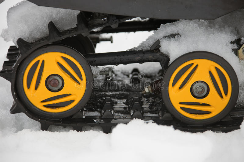 Rollers yellow and black caterpillars of the snowmobile with the. Snow and water. Close-up, drops, parts, tires, winter stock photography