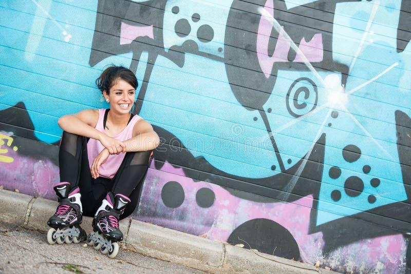 rollerskate微笑的年轻深色的妇女 免版税库存图片