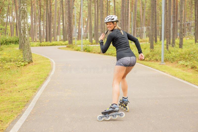 Rollerskating de la mujer y mirada detrás imagen de archivo