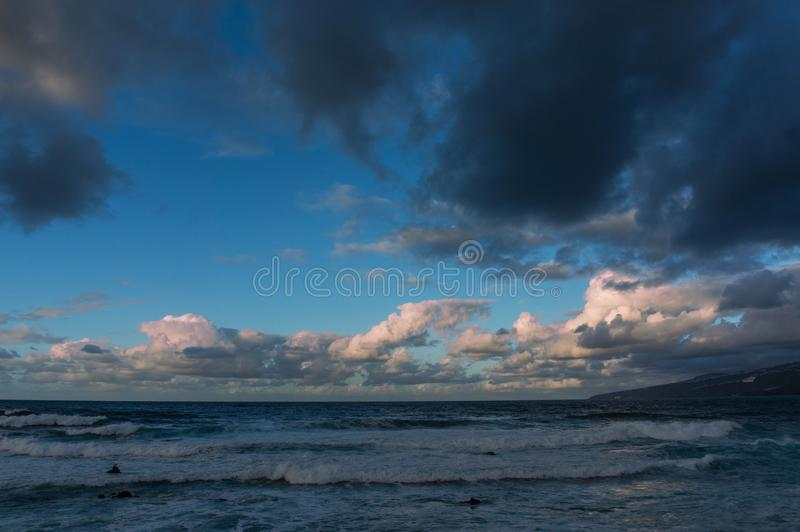 Rolling cloudscape over sea waves. Rolling cloudscape over seawaves. Expressive dark and light cumulus clouds. Foam on the crests of the waves. Marine postcard stock photography