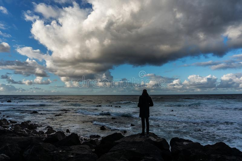Rolling cloudscape over a silhouette of a standing man in front of sea waves. Dramatic marine photo with expressive clouds in the blue sky. Twilight time royalty free stock image