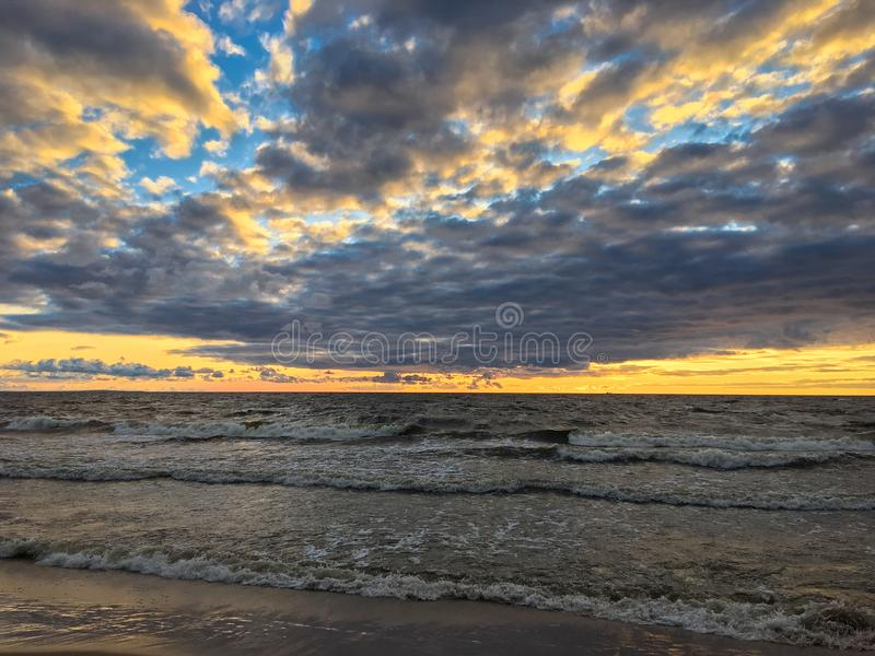 Rolling dark sea waves on sandy beach with dramatic sunset sky, the Gulf of Finland. Russia royalty free stock photos