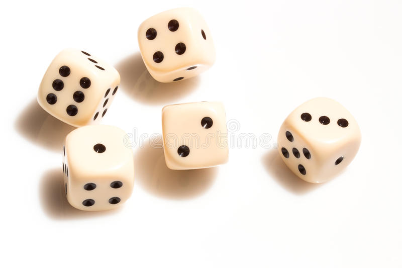 Rolling dice on white tabletop stock image
