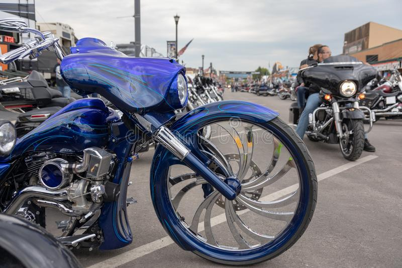 Rolling down Main Street in Sturgis, South Dakota, past a stunning custom motorcycle. SUNDAY, AUGUST 5, 2018, STURGIS, SD: A motorcyclist and passenger roll stock images