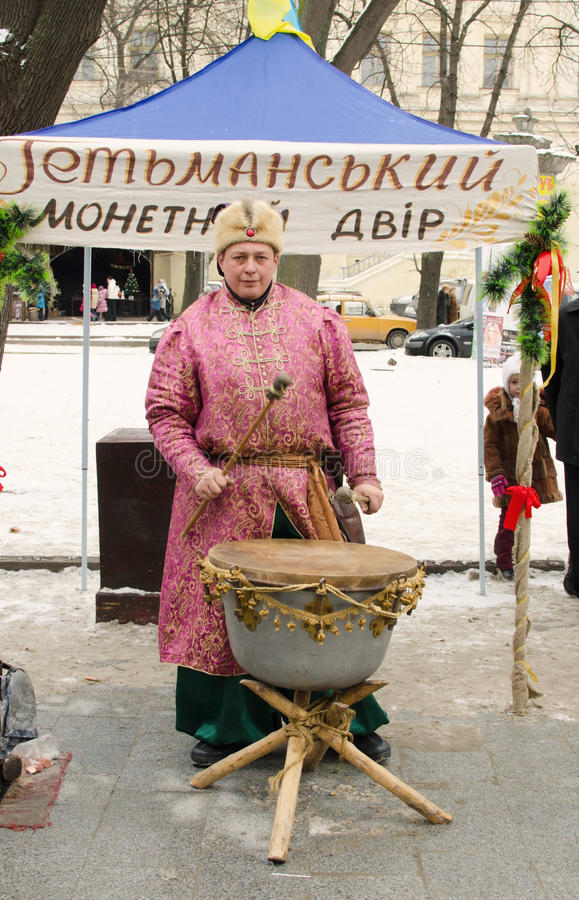 Rolling on the drums. Man in traditional Ukrainian dress on the city fair during Christmas season 2013 in Lemberg, West Ukrainian city royalty free stock image