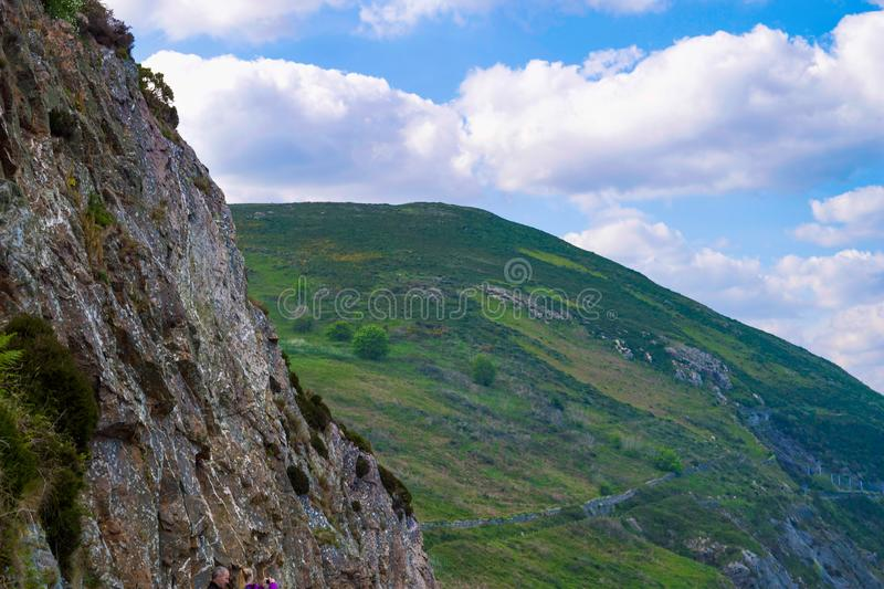 Rolling green hills and cliff face in Wicklow, Ireland with blue sky and white fluffy clouds in summer. Bright sunny day royalty free stock images