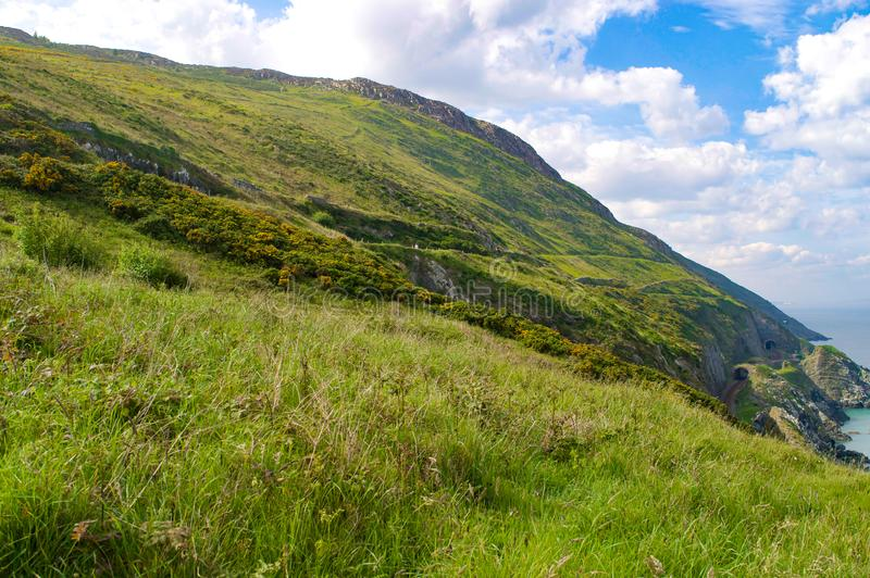 Rolling green hills and cliffs in Wicklow, Ireland with Irish sea on right. Bright sunny day in summer stock photo