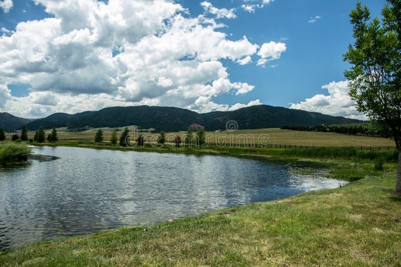 Rolling Hills med blåa molniga himlar, ett långt staket och en sjö arkivbild