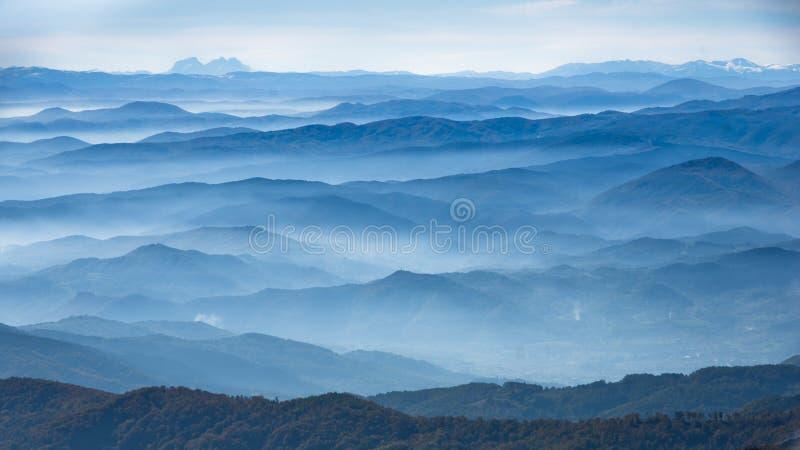 Rolling Hills och berg på den soliga dagen för höst med dimma, sikt från det Zeljin berget arkivfoton