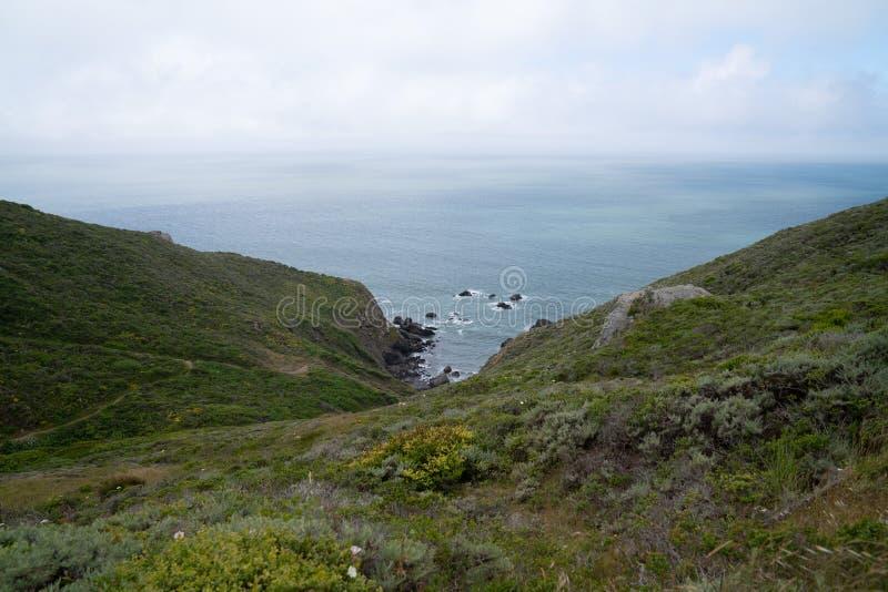 Rolling Hills und Wanderwegführung unten in eine felsige Bucht im Ozean lizenzfreie stockbilder
