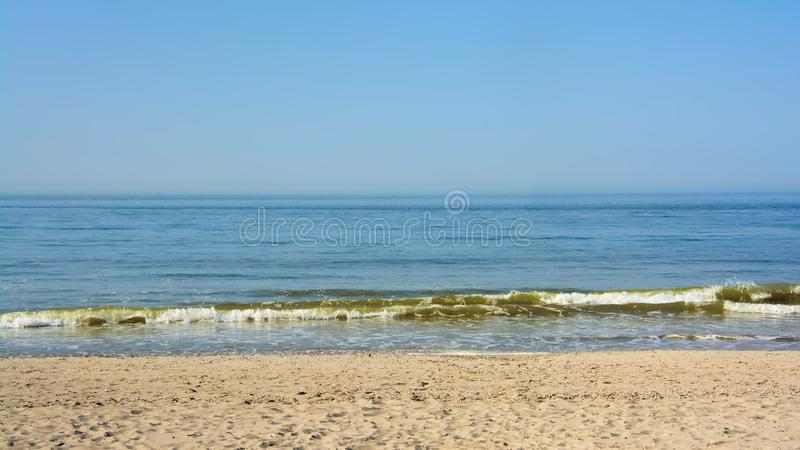 Rolling north sea waves on a Flemish beach under a blue sky. Rolling north sea waves under a blue sky on the beach of Ostend, Flanders, Belgium royalty free stock photo