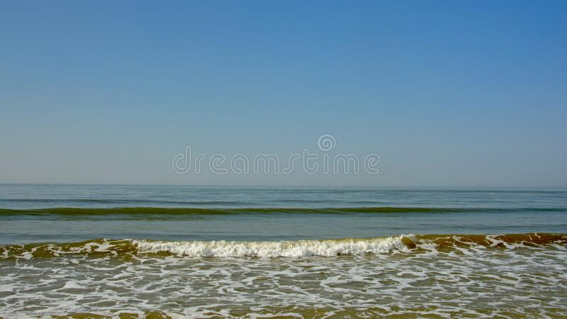 Rolling north sea waves under a blue sky. Rolling north sea waves under a blue sky in Ostend, Flanders, Belgium stock image