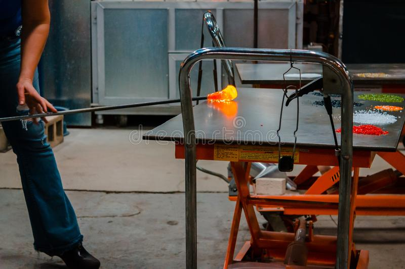 Rolling out molten glass to blow into a bowl. During a demonstration royalty free stock photo