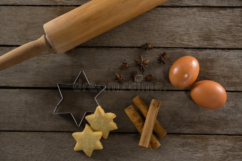 Rolling pin with eggs, cookie cutter, cookies, cinnamon and anise stock photo