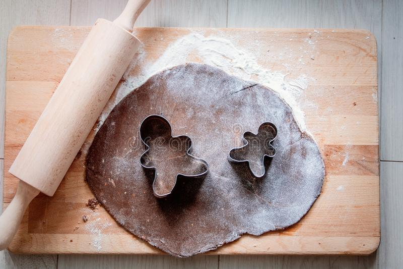 Rolling pin and metal forms for gingerbread man. On wooden table stock photo