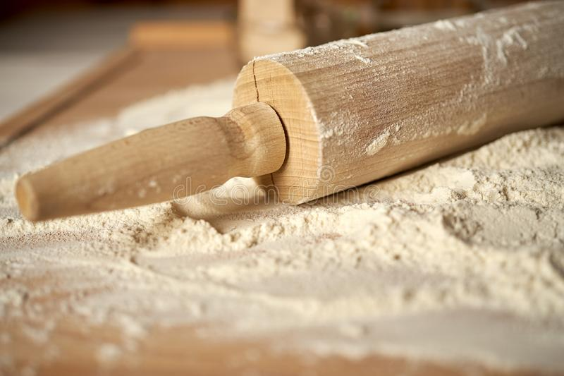 Rolling pin on pastry board sprinkled with flour on wooden  table royalty free stock photography
