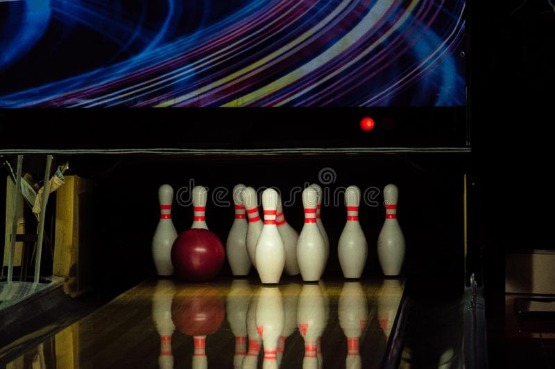Rolling red ball knocks down pins on a bowling alley lane.  stock image