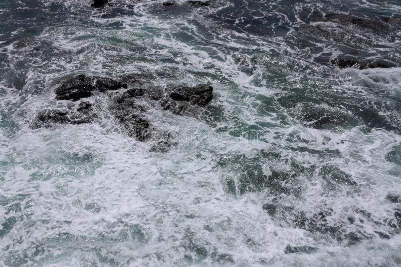 Rolling sea waves slamming on rocks. Top view royalty free stock images