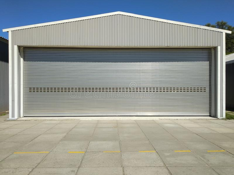 Rolling shutter door of large garage warehouse entrance with concrete blocked floor, industry building background with blue sky. Front view of garage with royalty free stock image
