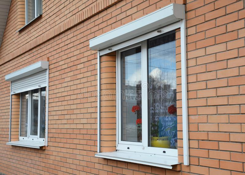 Rolling shutters house windows protection. Brick house with metal roller shutters on the windows. Photo stock photo