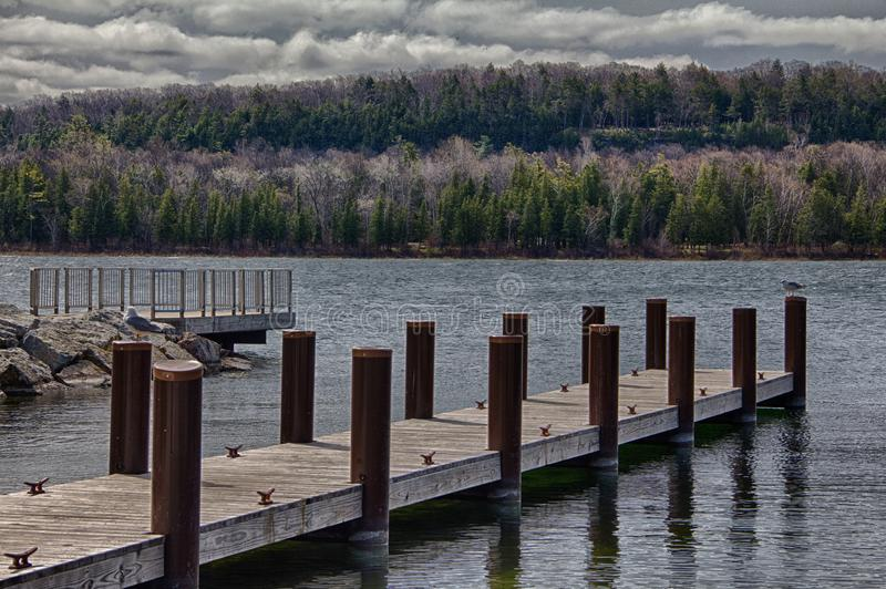 Wooden Piers Along Door County, WI Shoreline. Rolling storm clouds sit atop the tree-lined shore of Door County, Wisconsin. Two wooden piers jut obliquely into stock photo