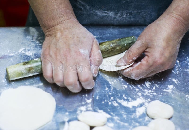 Rolling the stuffed dumpling skin stock images