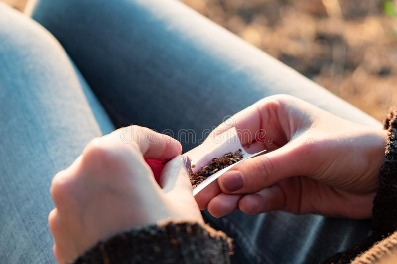 Rolling a tobacco cigarette. Close up image of female hands making a joint outdoors in sunlit background stock photo