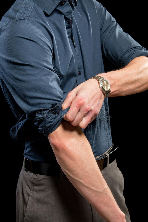 Rolling up Sleeves. Adult man rolling up his sleeves. Studio shot over black royalty free stock photos