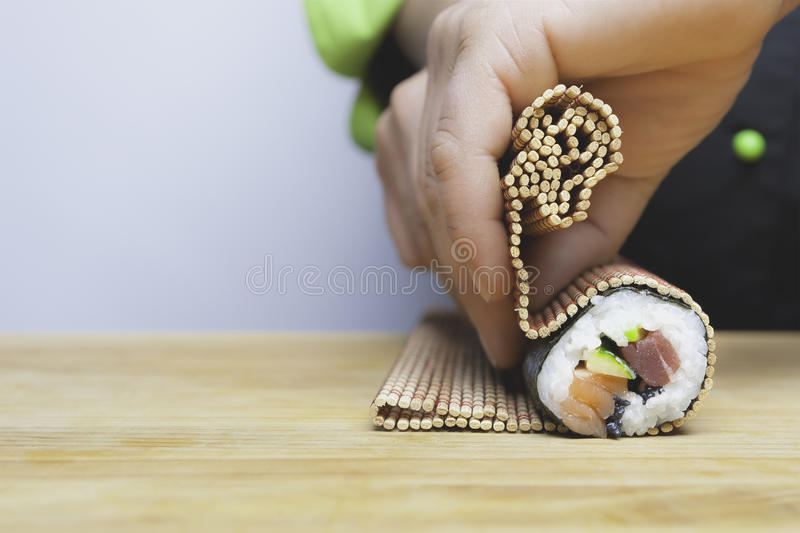 Rolling up sushi stock photography