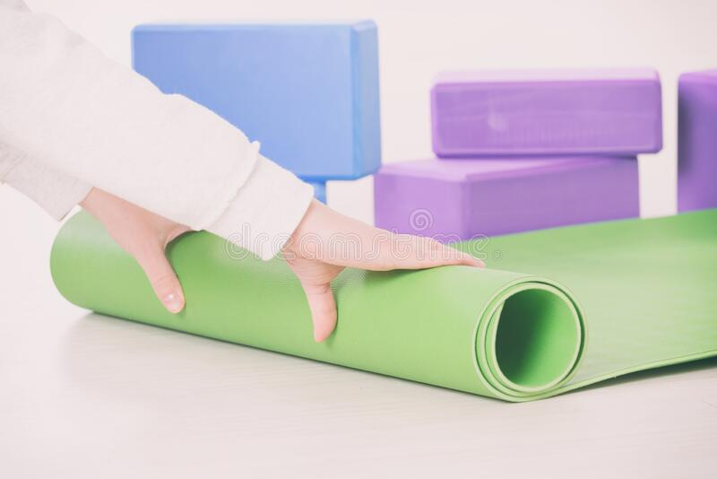 Rolling up a yoga mat royalty free stock images