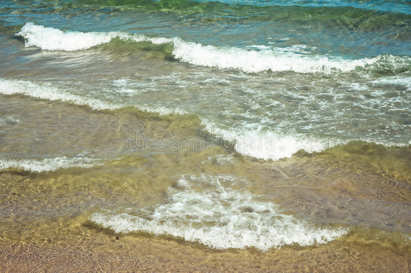 Rolling waves of an aquamarine sea and a sand beach on a sunny day. Rolling waves of a clear aquamarine sea and a sand beach on a sunny day stock image