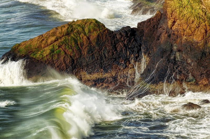Rolling Waves at Cape Disappointment. Rolling waves head for rocky shoreline at Cape Disappointment in ILwaco, on the Washington Coast royalty free stock photos