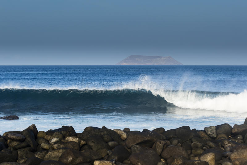 Rolling waves, island and rocks. At North Seymour, Galapagos stock image