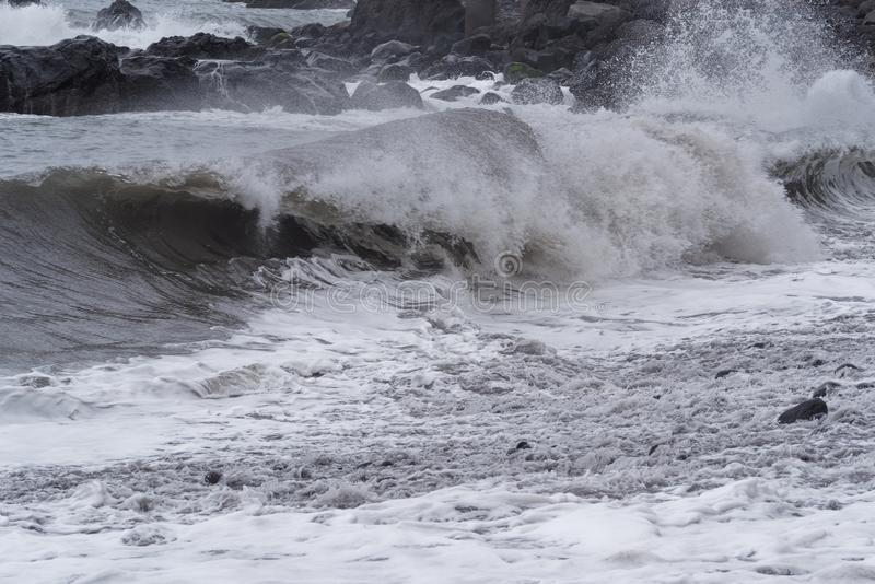 Rolling waves on stone coastline at stormy weather. Portuguese island of Madeira royalty free stock photography