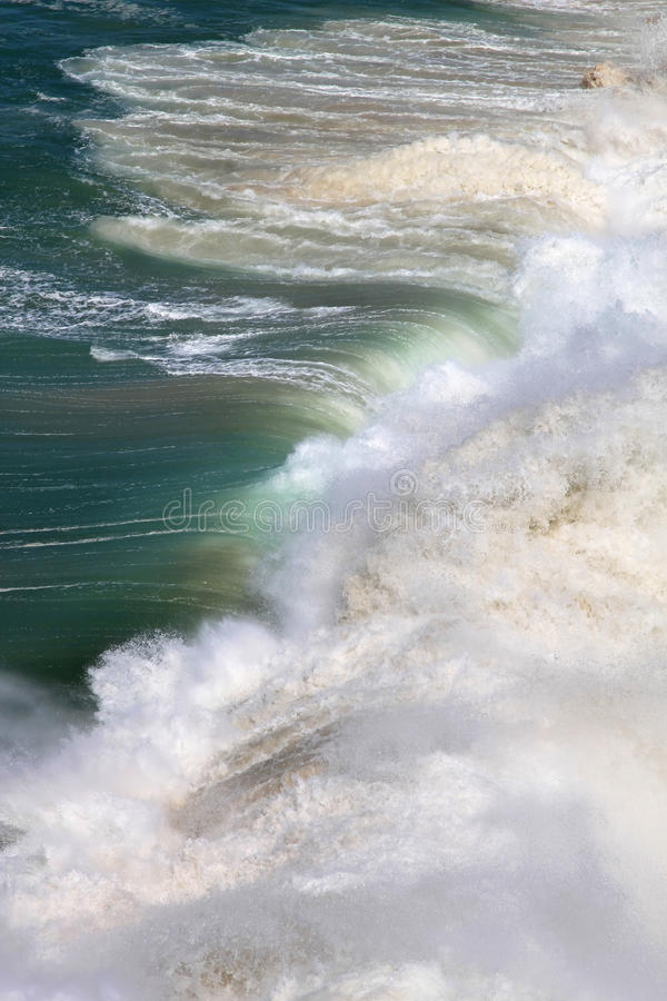 Rolling waves in sunlight, Atlantic Ocean. During flood large colourful waves of the Atlantic Ocean are rolling upon the beach of Pedro do Guilhim in Portugal stock image