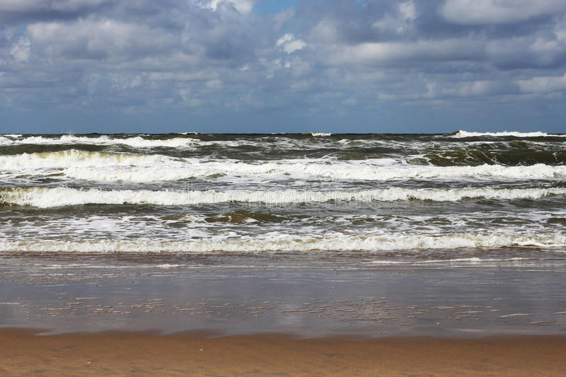 Rolling waves towards the beach. With a cloudy sky in the distance royalty free stock image