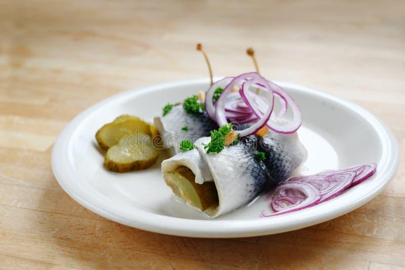 Rollmops o aringa marinata rotolata con le cipolle rosse, i cetriolini ed i capperi, una prima colazione acida di postumi di una  fotografia stock libera da diritti