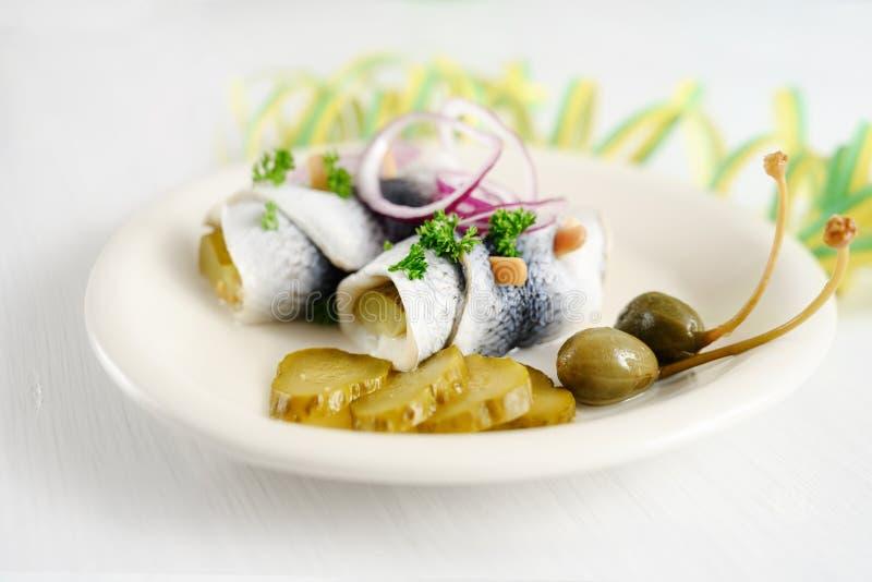 Rollmops o l'aringa marinata rotolata con le cipolle rosse, i cetriolini ed i capperi su una tavola bianca con la fiamma del part immagini stock libere da diritti