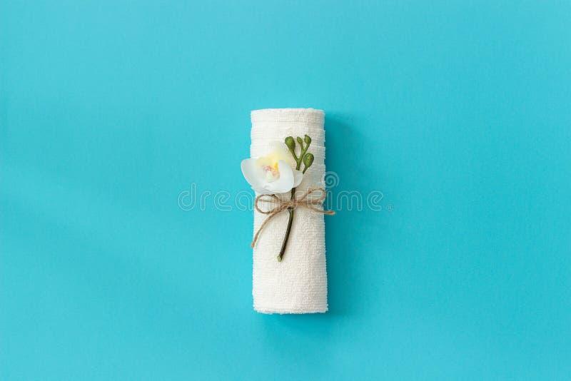 Rollo blanco de la toalla atado con la cuerda con la puntilla de la flor de la orquídea en fondo de papel azul Plantilla del espa fotos de archivo