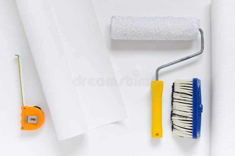 Rollo blanco del papel pintado con el rodillo de pintura, cepillo, cinta métrica fotos de archivo