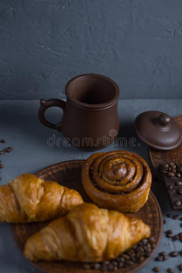 Rollo con canela y el cruas?n en un fondo gris y una taza de caf? con una barra de chocolate fotos de archivo