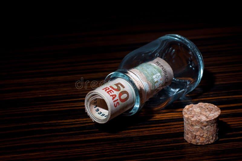 Rollo de 50 billetes de banco brasileños de los Reais dentro de una botella fotos de archivo