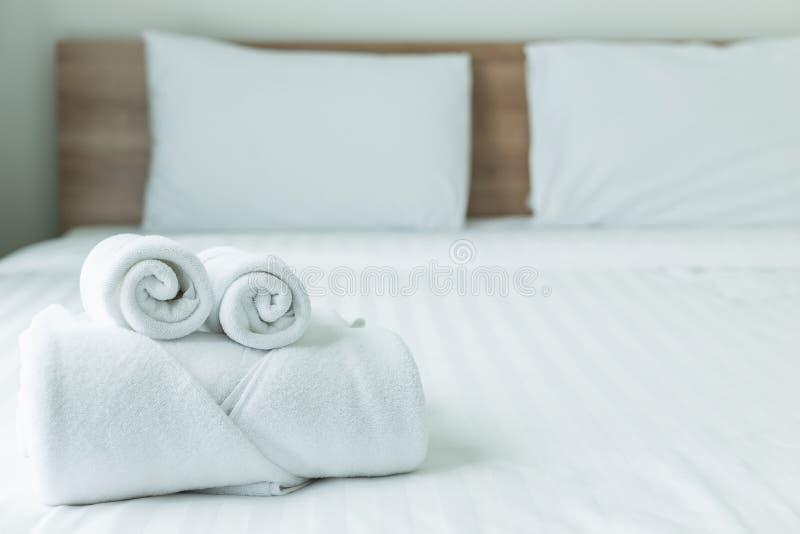 Rollo de la toalla blanca en la tabla de la cama en la habitación moderna de lujo foto de archivo libre de regalías