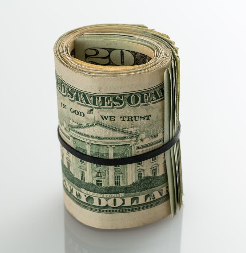 Rollo de $20 billetes de dólar en la tabla blanca fotografía de archivo