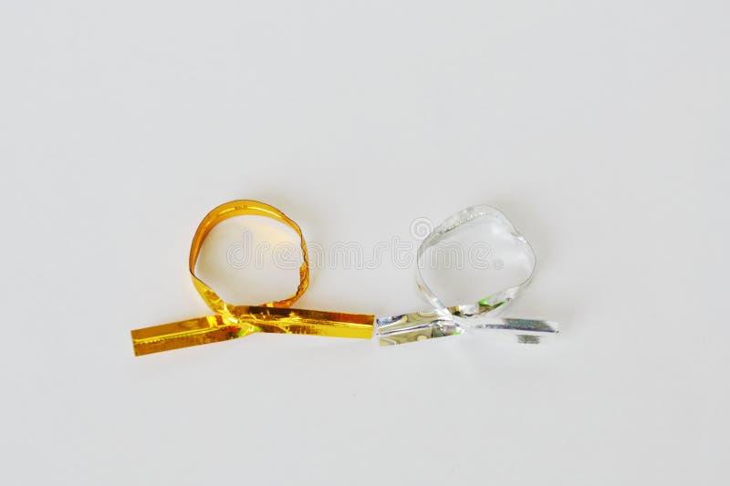 Rollo de oro y de plata del lazo de torsión en el fondo blanco fotografía de archivo